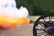 A close up shot of a Civil War cannon firing at a civil war re-enactment.
