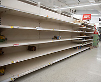 Empty shelves at Sainsburys Bicester as people stockpile food and cleaning supplies as fears grow of a 14 day quarantine uk photo by brian Jordan