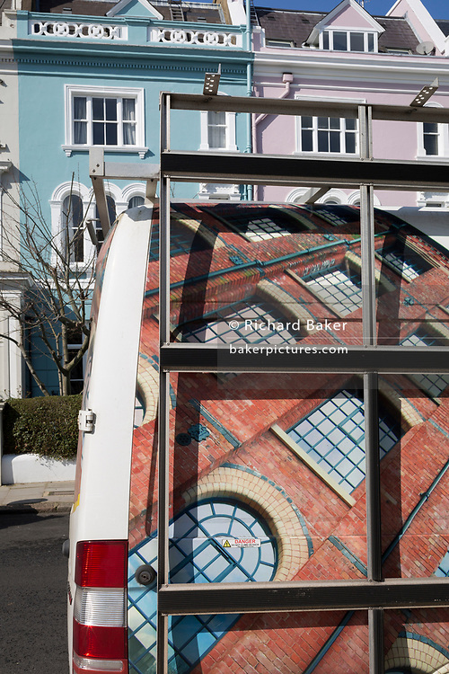 The design on the rear doors of a bespoke window company's van and Victorian houses along Elgin Crescent W11 in Notting Hill, on 13th March 2018, in London, England. Elgin Crescent's houses were built in the 1850s and 1860s with many now listed buildings. East of Ladbroke Grove, it was originally called Elgin Road. It is named after the town of Elgin in Scotland.