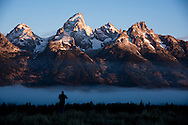 A photographer and his tripod at Glacier Overlook pullout overlooking the teton range at sunrise in Grand Teton National Park outside Jackson, WY. ©Brett Wilhelm