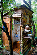An outside lavatory, for a family living high in the Corbieres hills below the Pyrenees, on their land, which is without electricity. The wooden hut among the trees is environmentally friendly and the waste is used to fertilise the garden.