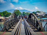 "09 JANUARY 2019 - KANCHANABURI, THAILAND: Tourists walk across the ""Bridge On the River Kwai"" in Kanchanaburi. Hundreds of thousands of Asian slave laborers and Allied prisoners of war died in World War II constructing the ""Death Railway"" between Bangkok and Rangoon (now Yangon), Burma (now Myanmar) for the Japanese during World War II.  The bridge is now one of the most famous tourist attractions in Thailand.       PHOTO BY JACK KURTZ"