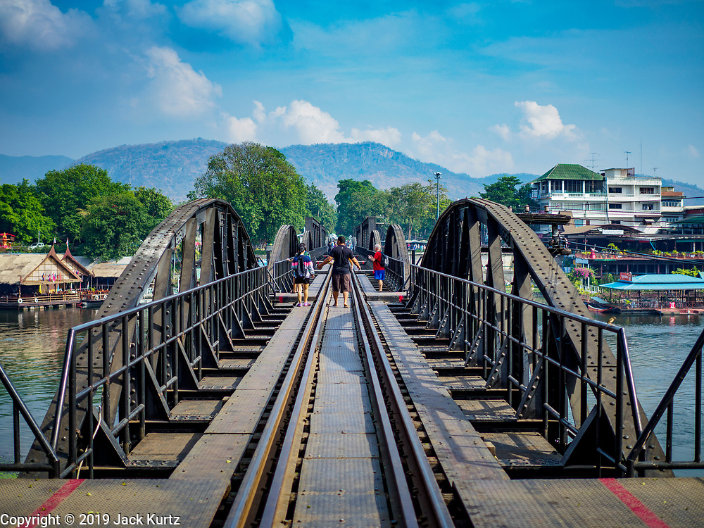 """09 JANUARY 2019 - KANCHANABURI, THAILAND: Tourists walk across the """"Bridge On the River Kwai"""" in Kanchanaburi. Hundreds of thousands of Asian slave laborers and Allied prisoners of war died in World War II constructing the """"Death Railway"""" between Bangkok and Rangoon (now Yangon), Burma (now Myanmar) for the Japanese during World War II.  The bridge is now one of the most famous tourist attractions in Thailand.       PHOTO BY JACK KURTZ"""