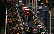 Seen from an office block high vantage point, thousands of commuters pour northwards over London Bridge against the direction of queueing buses and cars. It is a scene about the transient business community and mass transport. The working population arrives early for work over the bridge in the City of London's historic financial district. We see the sunlit faces of those walking towards the viewer which echo the red tail lights of the stationary vehicles. So gridlocked is the traffic on the southbound carriageway, there is a lone cyclist stuck and squeezed between the curb and a double-decker bus. The City of London has a resident population of under 10,000 but a daily working population of 311,000. The City of London is a geographically-small City within Greater London, England.