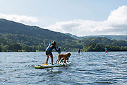 A woman and two dogs on a stand up paddleboard on Lake Grasmere on the 13th June 2019 in the Lake District in the United Kingdom. Lake Grasmere is also known River Rothay and is near the town of Grasmere in the Lake District in Cumbria.
