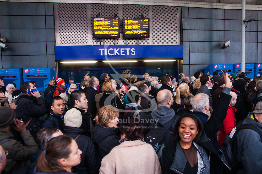 Finnsbury Park, London, December 27th 2014. All trains in and out of King's Cross, one of the busiest stations in London, have been cancelled thanks to engineering work on the East Coast mainline overrunning. A limited sevice is running from Finnsbury Park station which has become heavily congested, with British Transport Police called in to assist with crowd control. PICTURED: Travellers crowd the forecourt of Finnsbury Park station as they await their turn to enter the congested station.
