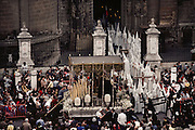 A procession leaving the cathedral during holy week in Seville, Spain. Street processions are organized in most Spanish towns each evening, from Palm Sunday to Easter Sunday. People carry statues of saints on floats or wooden platforms, and an atmosphere of mourning can seem quite oppressive to onlookers.