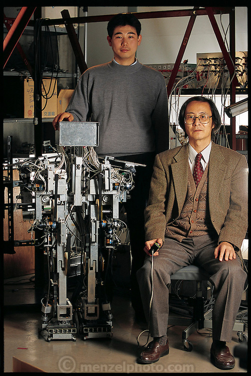 """Posing for a portrait at the Osaka  (Japan) University Department of Computer-Controlled Mechanical Systems, Junji Furusho (seated) and research associate Masamichi Sakaguchi show off Strut, their child-sized humanoid robot. At the time, the robot, a work in progress, could not walk at all?it could only stand. (It walked sometime later.) But simply getting the robot to stand properly was a major accomplishment. Like a human being, Strut has such complex, interreacting mechanical """"musculature"""" that considerable processing power is needed simply to keep it erect. Japan. From the book Robo sapiens: Evolution of a New Species, page 49."""