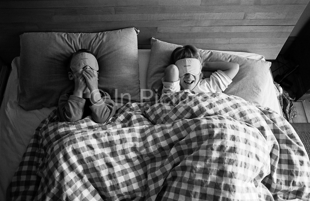 """Looking down on them from above, we see a brother and sister play with free airline blindfolds while in their parents' bed at the family home in South London. Pretending to be blind, they giggle at this hilarious and childish game as if acting out the speak and see no evil. From a personal documentary project entitled """"Next of Kin"""" about the photographer's two children's early years spent in parallel universes. Model released."""