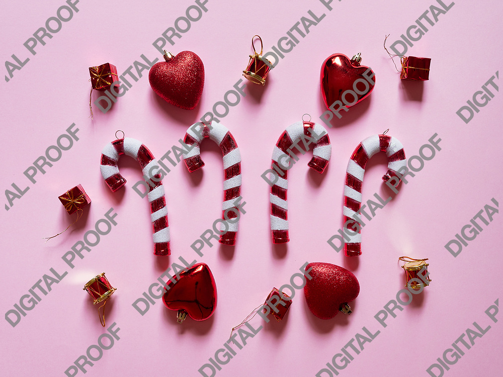 Christmas candy cane drums hearts and gifts at studio above view over a pink background isolated flatlay