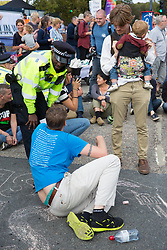 London, UK. 3 September, 2019. A Metropolitan Police officer tries to disperse one of hundreds of Quakers, joined by fellow peace activists and representatives of other faith groups, holding a religious service in the access road outside ExCel London as part of the day's No Faith In War activities in protest against DSEI, the world's largest arms fair.