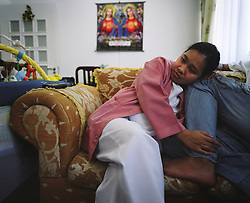 Rosalie Villanueva, 35, relaxes with her husband Christopher Villanueva after working the night shift at the Al Rahba Hospital in Abu Dhabi, United Arab Emirates on Feb. 2007.  Rosalie met her husband while they were both OFWs working in Saudi Arabia. They both later got jobs in Abu Dhabi, but decided to leave one of their three children, Precious Lara, with Rosalie's parents in the Philippines. Isolation and damaged family relations due to time spent apart is one of the major sacrifices made by OFWs.