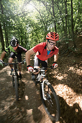 Mountain bikers riding on track through forest, Bavaria, Germany