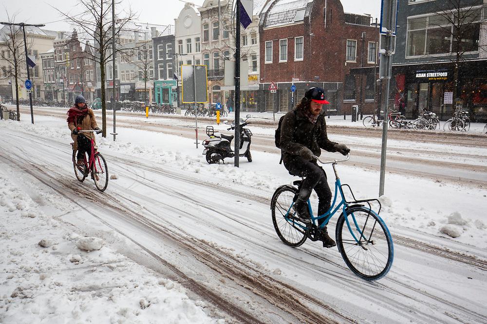 In Utrecht rijden fietsers door de sneeuw. Nederland geniet van de eerste sneeuw sinds lange tijd.<br /> <br /> In Utrecht cyclists ride in the snow. People in the Netherlands enjoy the first snow since years.