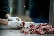 Cook uses a saw to cut meat in a restaurants kitchen