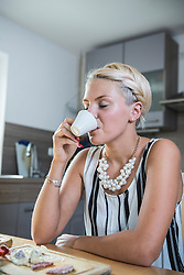 Young woman drinking coffee in the kitchen, Bavaria, Germany