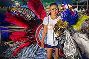 23 NOVEMBER 2013 - BANGKOK, THAILAND:  A cast member of the Prathom Bunteung Silp mor lam troupe picks up her feathered headdress before a performance in Bangkok. Mor Lam is a traditional Lao form of song in Laos and Isan (northeast Thailand). It is sometimes compared to American country music, song usually revolve around unrequited love, mor lam and the complexities of rural life. Mor Lam shows are an important part of festivals and fairs in rural Thailand. Mor lam has become very popular in Isan migrant communities in Bangkok. Once performed by bands and singers, live performances are now spectacles, involving several singers, a dance troupe and comedians. The dancers (or hang khreuang) in particular often wear fancy costumes, and singers go through several costume changes in the course of a performance. Prathom Bunteung Silp is one of the best known Mor Lam troupes in Thailand with more than 250 performers and a total crew of almost 300 people. The troupe has been performing for more 55 years. It forms every August and performs through June then breaks for the rainy season.              PHOTO BY JACK KURTZ