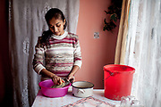 Jana, 23 year old wife of Emil (20) and mother of a son and a daughter is preparing lunch for her family in their new built house in Rankovce. The young family corporates with the foundation ETP Slovakia which has a project in Rankovce setting up micro-loan funds for the local Roma community. Loans from this fund enabled families to build their own low-cost brick homes, on land they own.