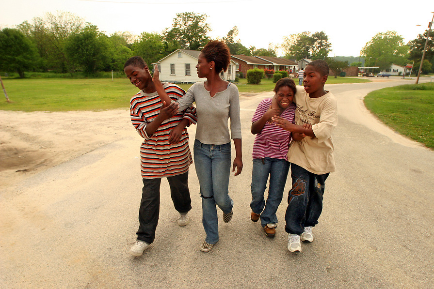 """Siblings, Mario Wright, left, Tia McLeod, Precious Wright, and Marvin Wright joke around as they walk home from the neighborhood store. All four go to school in Dillon 2. """"I love my brothers and sisters, I've always tried to take care of them. They're almost like my children,"""" said Tia."""