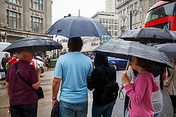 © Licensed to London News Pictures. 19/08/2016. London, UK. People take shelter from the rain underneath umbrellas on Oxford Street in London on 19 August 2016. Photo credit: Tolga Akmen/LNP