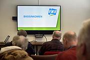 Nederland, Nijmegen, 25-1-2019Bij het regiokantoor van de FNV is een bijeenkomst met uitkeringsgerechtigden . Een vakbondsbestuurder houdt een praatje en een enquete over het basisinkomen . De aanwezige leden kunnen een voorkeur voor een ja of nee antwoord aangeven door een rode of groene kaart op te houden .Foto: Flip Franssen