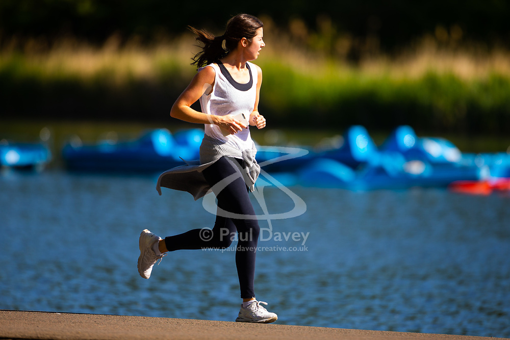 A woman runs past the boarding lake on a bright spring morning in Regents Park London. London, May 14 2019.