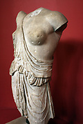 Torso of an Amazon. Five bronze statues of defeated Amazons had been made by famous Greek artists for the sanctuary of Artemis at Ephestas.  According to the legend the Amazons returned to Ephesus which they had founded on their way to war with Athens.  This Amazon was leaning against a pillar, her right arm on her head, a deep would on her right side.  Reins serve her as a belt, she may be the Amazon queen Hippolyte who had lost her famous belt to a Greek opponent.