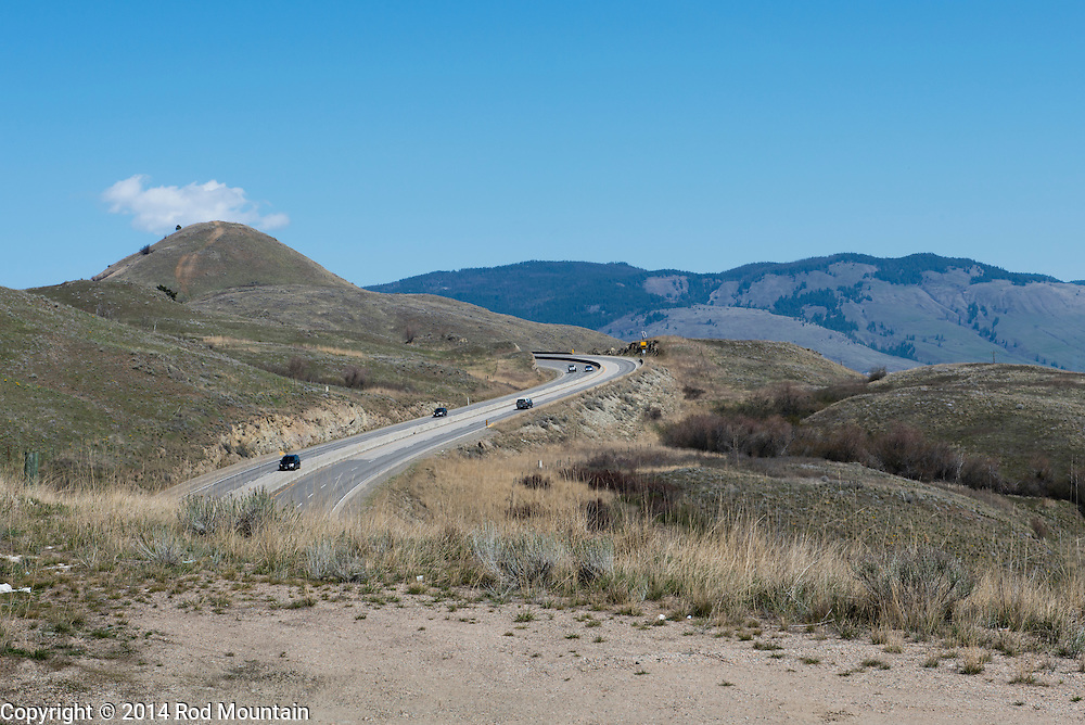 A new section of highway winds around and over the hillside towards Vernon, British Columbia.