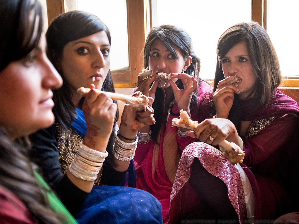 Bride maids eating mutton off the bone at a village wedding ceremony.