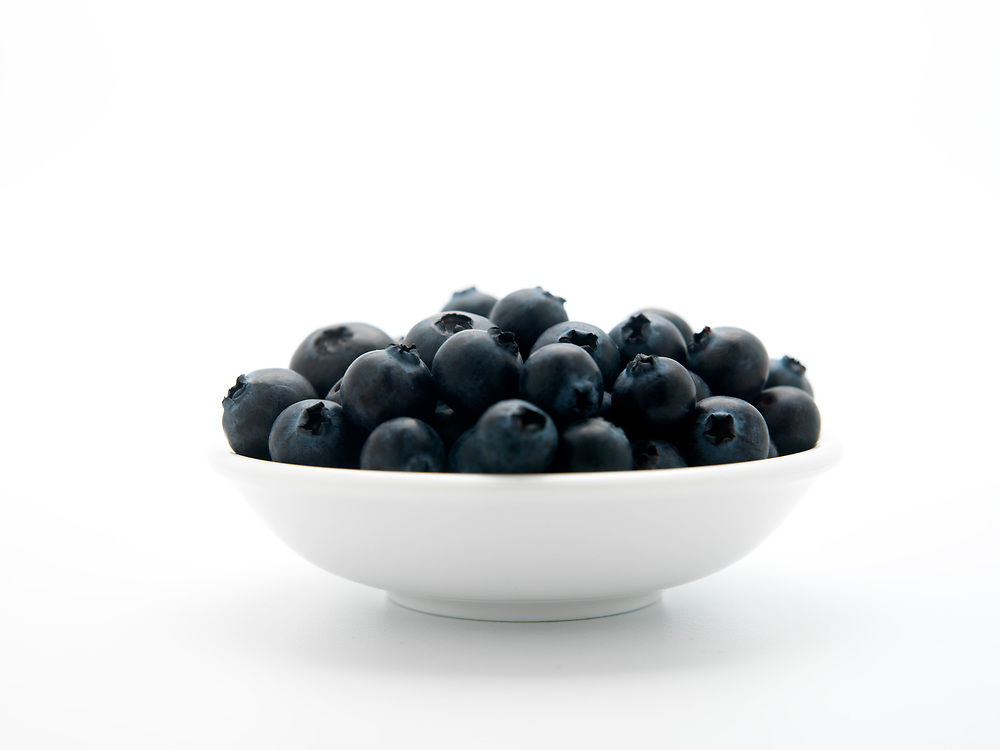 Bowl of fresh raw blueberries on a white background