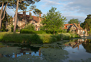 A 12th century moat surrounding the garden and Tudor manor house at sunrise at Hindringham Hall, Hindringham, Norfolk, UK