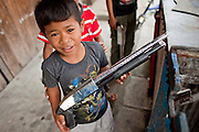 """Sept. 27, 2009 -- TAK BAI, THAILAND: Thai Muslim boys play with toy shotguns in front of their home in Tak Bai, Narathiwat, Thailand. Thailand's three southern most provinces; Yala, Pattani and Narathiwat are often called """"restive"""" and a decades long Muslim insurgency has gained traction recently. Nearly 4,000 people have been killed since 2004. The three southern provinces are under emergency control and there are more than 60,000 Thai military, police and paramilitary militia forces trying to keep the peace battling insurgents who favor car bombs and assassination.   Photo by Jack Kurtz"""
