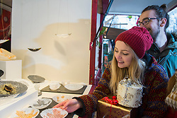Young woman looking at glass plates at market stall
