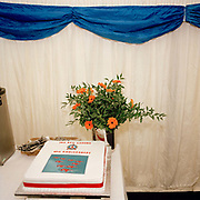 A 40th anniversary celebration cake has been baked for the elite 'Red Arrows', Britain's prestigious Royal Air Force aerobatic team who are soon to appear. Displayed in a hospitality tent at the Kemble Air Show, the iced gateau has a red ribbon and an image of nine aircraft in mid-flight. A bouquet of flowers and assorted cutlery for the forthcoming lunch is alongside. Blue paper is draped over the top adding to the patriotic red, white and blue colours. After several identities, the Red Arrows started life near this location in 1964 at RAF Little Rissington in Gloucestershire. Their name originates from the French 'Fleches Noirs', or Black Arrows, so in England, a new team was established flying black Hawker Hunters in the colour of their Squadron 111. As the Red Arrows display team, they have since flown over 4,000 shows in 52 countries.