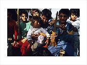 Roma Gypsy children with homemade toyguns, caught between the frontlines during the Balkans wars. Near Travnik, Bosnia 1994...Roma Gypsies left Rajasthan in India a thousand years ago, in the ninth and tenth centuries. They were pushed west by the Ottoman Muslim Empire as it moved through Persia towards the frontiers of Europe. They entered Europe in the foutrteenth century and were slaves in Romania and Moldavia until the mid 1850s. There are about 15 million Roma gypries in the world, about 12 million who live in Europe. they are Europe's largest ethnic minority. They have rich traditions and culture, their own language. They are renowned for their prowess in music and dance; they are also skilled craftsman, metal roofmakers, silver and goldsmiths. Their traveling and nomadic lifestyle which grew from a necessity to find work, and because they were often moved on from one place to the next, has given them both a liberty but also marks them as different and they are often feared by sedentary peoples, who label and scapegoat them. They are hardy survivors and live in the brunt of racism and prejudice, often marginalised, living in poverty, without proper human rights afforded to them..
