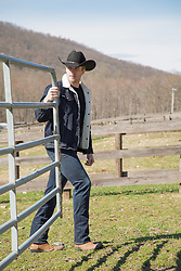 hot cowboy on a ranch closing a gate