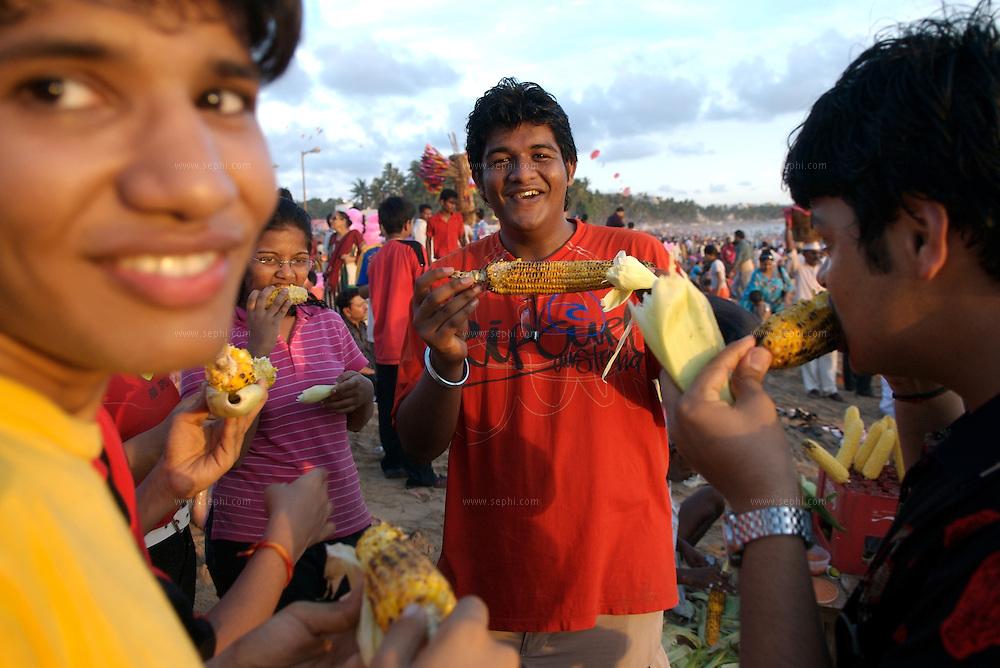 People enjoy corn on the cob on Juhu Chowpati beach in MUmbai, June 2007