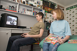 Boy playing a computer game and girl sitting on the bed reading a magazine in a bedroom,