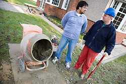 Builder talking to a customer whilst standing over cement mixer,