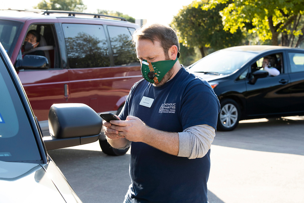 Catholic Charities workers including Deputy Registrar Justin Estep help Texas residents check voter registration status and help with voter applications during a four-hour drive October 1, 2020 in Austin.  Several dozen mostly Hispanic U.S. residents were signed up in the non-partisan effort.