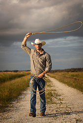 cowboy swinging a lasso while walking on a dirt road