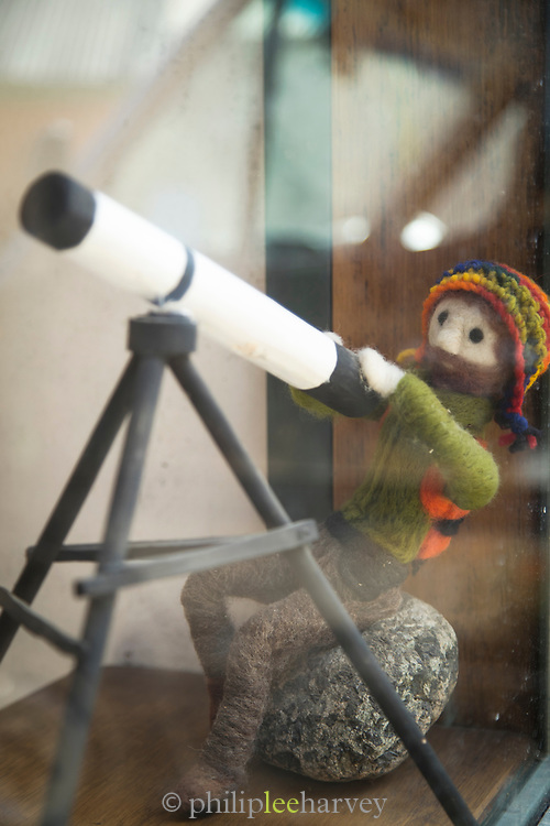 Close up of knitted figure using telescope in shop window, Pisco Elqui, Chile