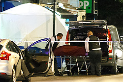 © Licensed to London News Pictures. 10/07/2015. London, UK. A body is taken to a private ambulance at a crime scene on Lordship Lane in Wood Green, north London where a man has died and a woman has been taken to hospital following an apparent drive-by shooting on Friday, July 10, 2015. Photo credit: Tolga Akmen/LNP