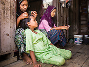 """28 FEBRUARY 2014 - MAE SOT, TAK, THAILAND: A Burmese Muslim woman fixes her daughter's hair in their home in Mae Sot. Mae Sot, on the Thai-Myanmar (Burma) border, has a very large population of Burmese migrants. Some are refugees who left Myanmar to escape civil unrest and political persecution, others are """"economic refugees"""" who came to Thailand looking for work and better opportunities.    PHOTO BY JACK KURTZ"""