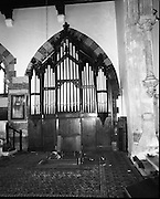 Pipe Organ Dismantling at Aungier Street.  (K86).1977..01.02.1977..02.01.1977..1st February 1977..A pipe organ built around 100 years ago for St Peter's Church (Church of Ireland),at Whitefriar / Aungier Street was being dismantled by Mr Gerry Smith and Mr Sam Wright of Dublin Organ Works. The organ was being dismantled for transfer to St Michael's Church,(Roman Catholic),in Blackrock,Co Cork..Picture shows the organ in position in St Peter's Church before being dismantled..Image shows the delicate operation of dismantling of the organ keyboard.