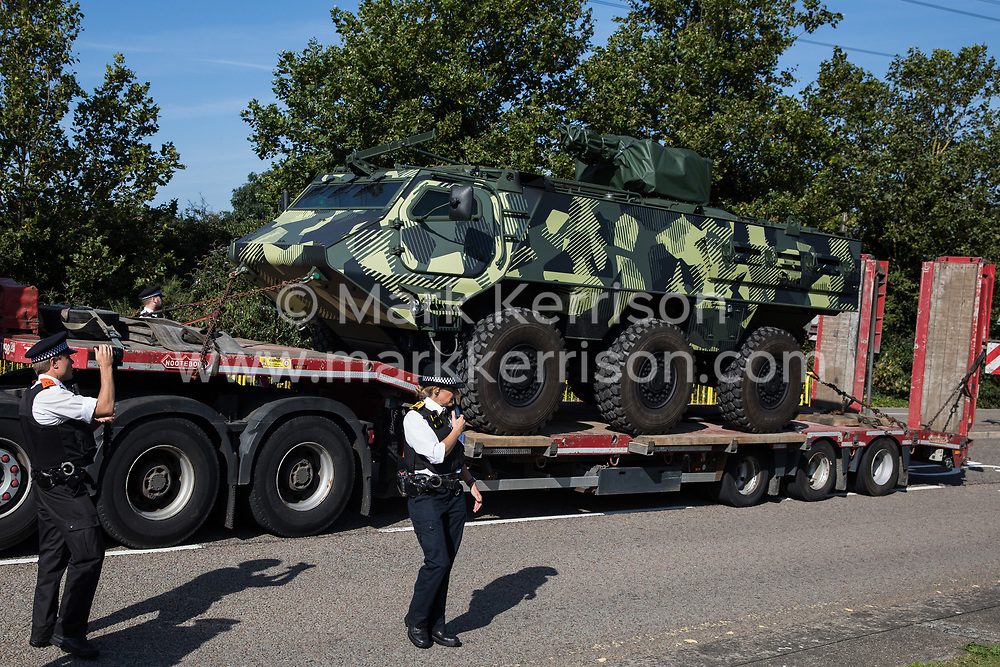 Metropolitan Police officers monitor a convoy of trucks delivering military equipment to ExCeL London for the DSEI 2021 arms fair on 8th September 2021 in London, United Kingdom. The third day of week-long Stop The Arms Fair protests outside the venue for one of the world's largest arms fairs was themed around demilitarising education.