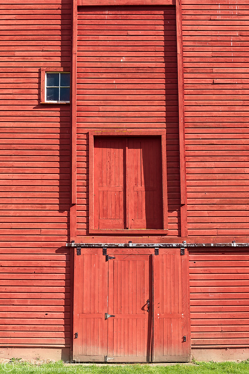 Doors on the side of the red Gambrel Roof Barn (built in 1939) on Len Rowlatt's farmland in Langley.  This farmland was first used by Joseph and Sarah Anne Annand and later by Len Rowlatt until his death in 1972.  The property is now part of Campbell Valley Regional Park in Langley, British Columbia, Canada.