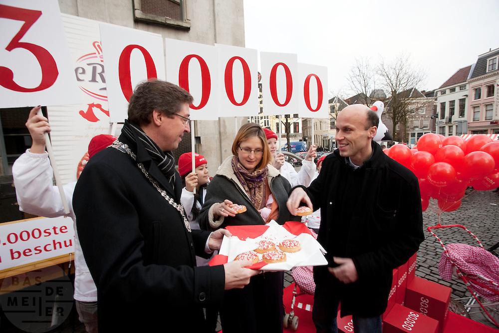 Burgemeester Wolfssen eet samen met Gert en Sandra Dijkhuizen het eerste beschuit met rood en witte muisjes. De muisjes zijn speciaal gemaakt om de 300.000e inwoner van Utrecht te vieren. De dochter Helena van familie Dijkhuizen bleek de 300.000e inwoner te zijn.