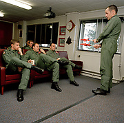 Squadron Leader Spike Jepson, leader of the elite 'Red Arrows', Britain's prestigious Royal Air Force aerobatic team, demonstrates the Corkscrew manoeuvre to his group of pilots and visitors in the briefing room at their RAF Scampton, Lincolnshire headquarters. Using two scaled model Hawk jet aircraft he shows how their formation is to be flown on their next training flight. Five autumn and winter months are spent teaching new recruits manual aerobatic display flying while the older members (who rotate positions) learn new disciplines within the routine. Their leaning curve is steep, even for these accomplished fast-jet aviators who had already accumulated 1,500 hours in fighters. By Summer they need every aspect of their 25-minute displays honed to perfection.