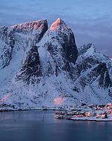 January winter sunrise illuminates mountain peaks rising over village of Reine, Moskenesøy, Lofoten Islands, Norway